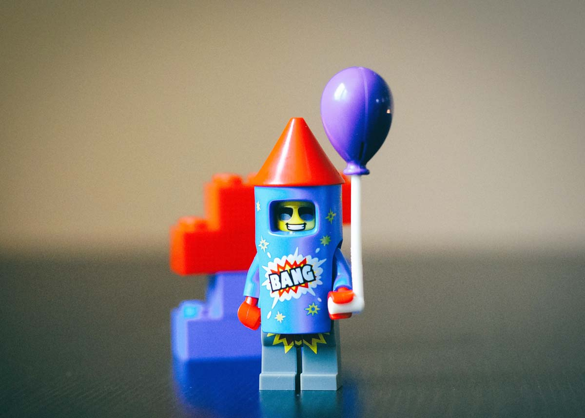 A little Lego firework rocket holding a Lego balloon.