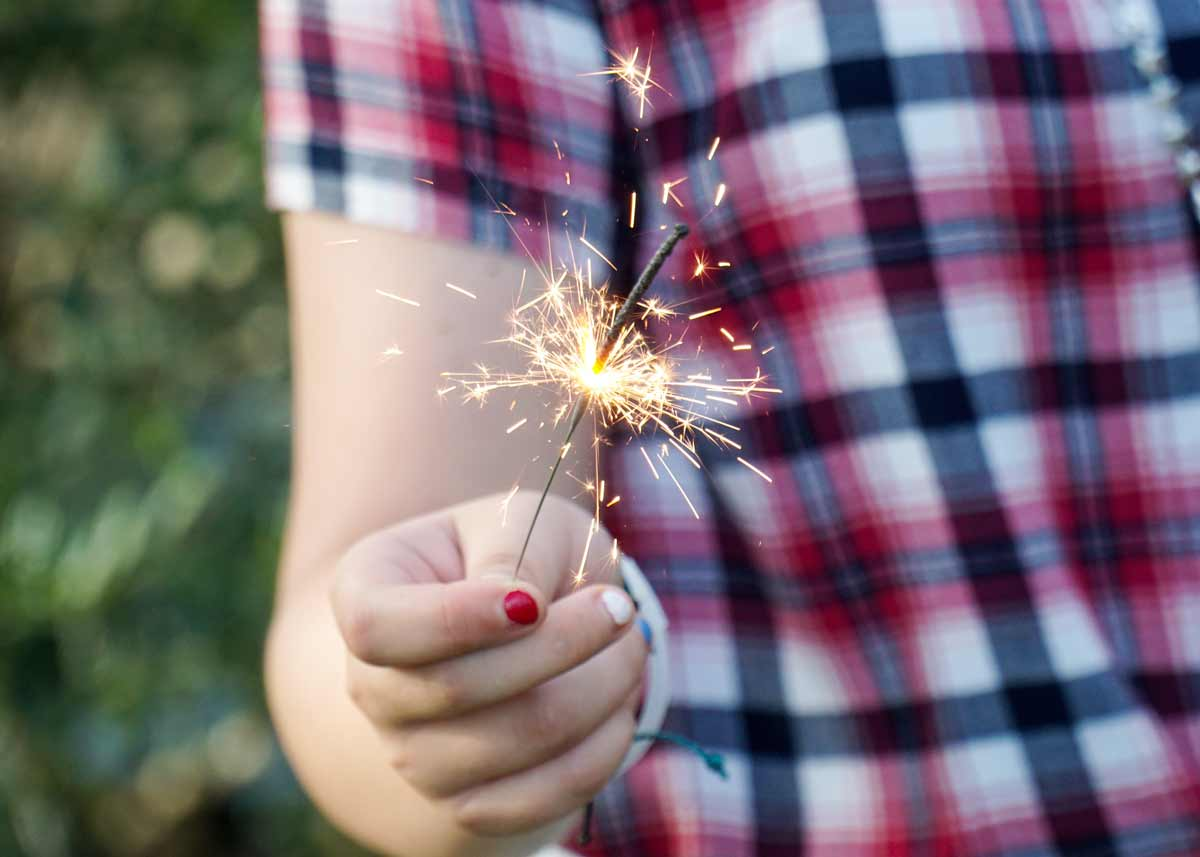 Close up of a child holding a sparkler.