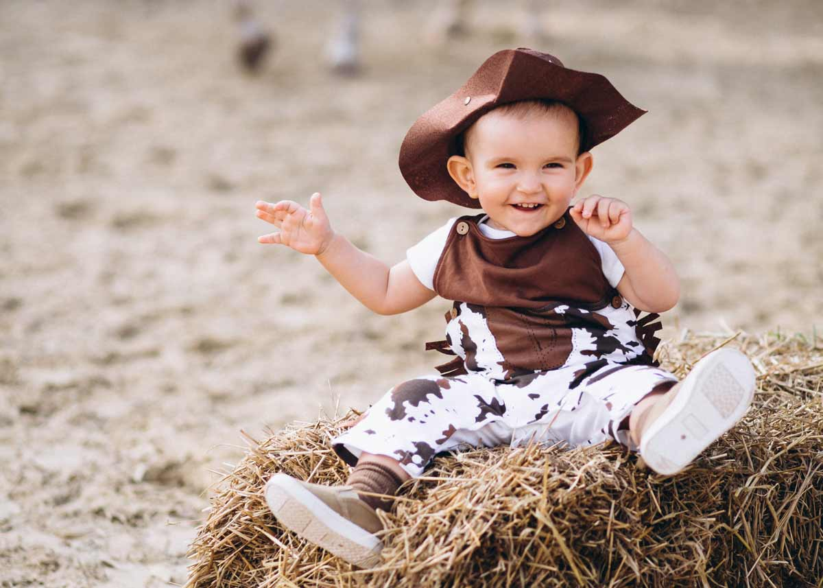 Baby boy dressed as a cowboy, smiling as he sits on a bale of hay.