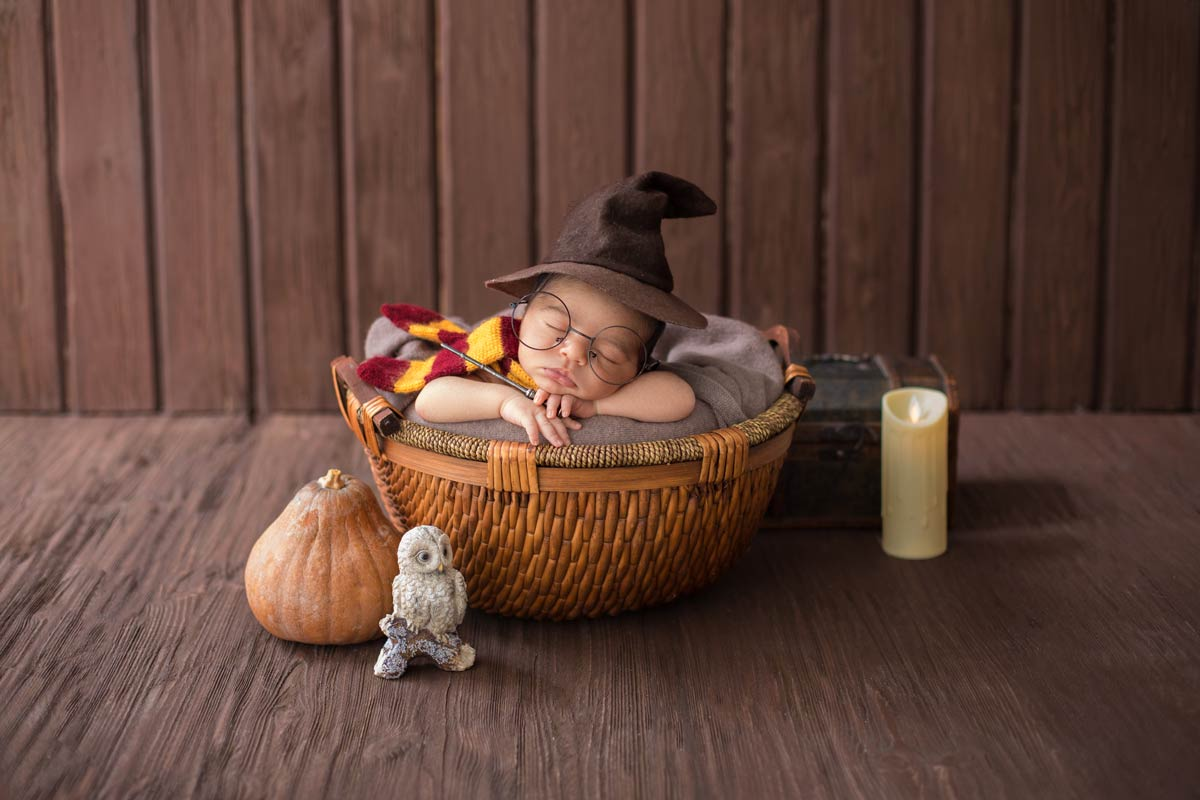 A newborn baby is fast asleep, dressed in a wizard's hat and Harry Potter glasses and surrounded by Harry Potter related items.