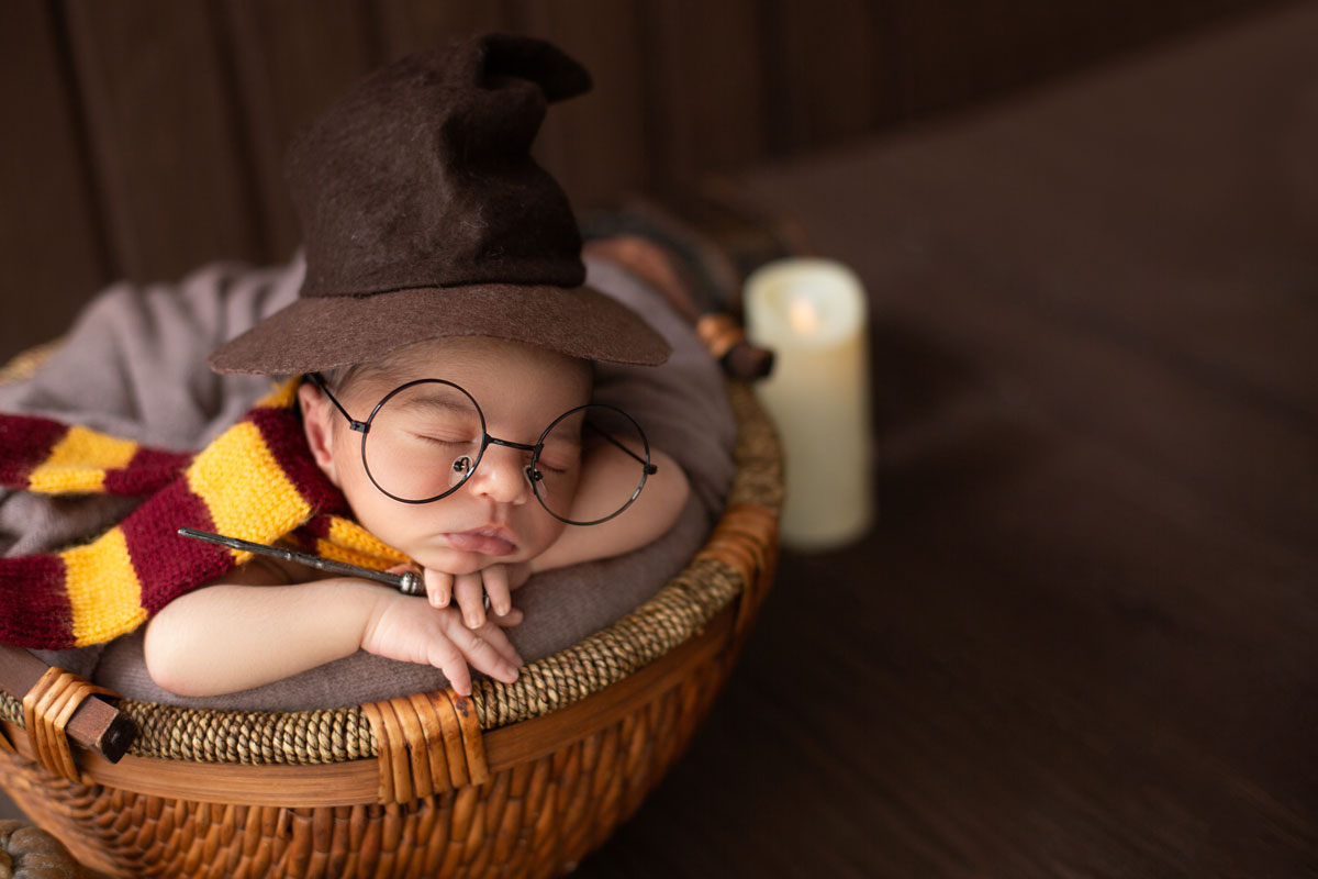 A close up image of a newborn baby wearing and wizard's hat and Harry Potter style glasses.