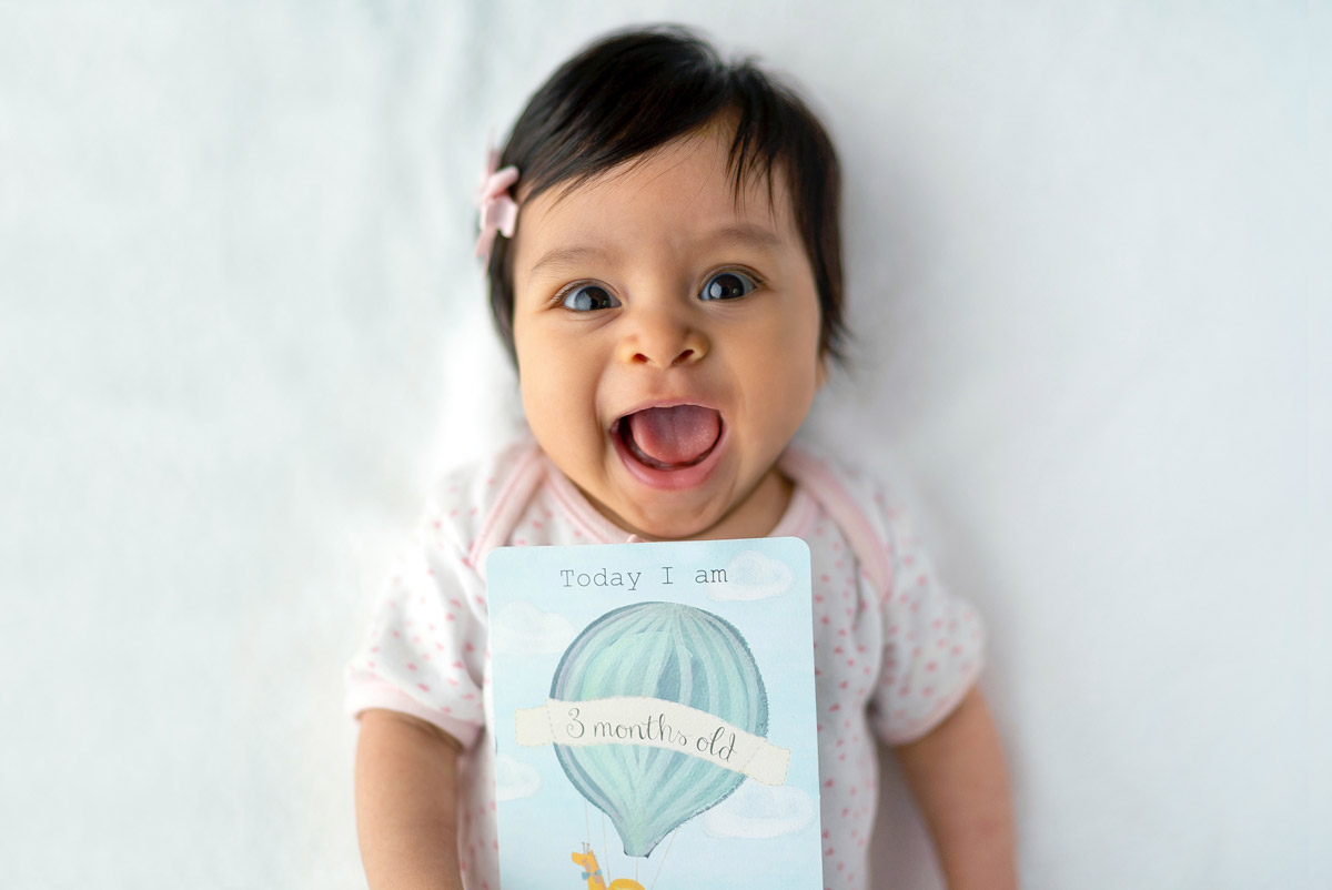 A young baby girl smiles at the camera with her mouth wide open.