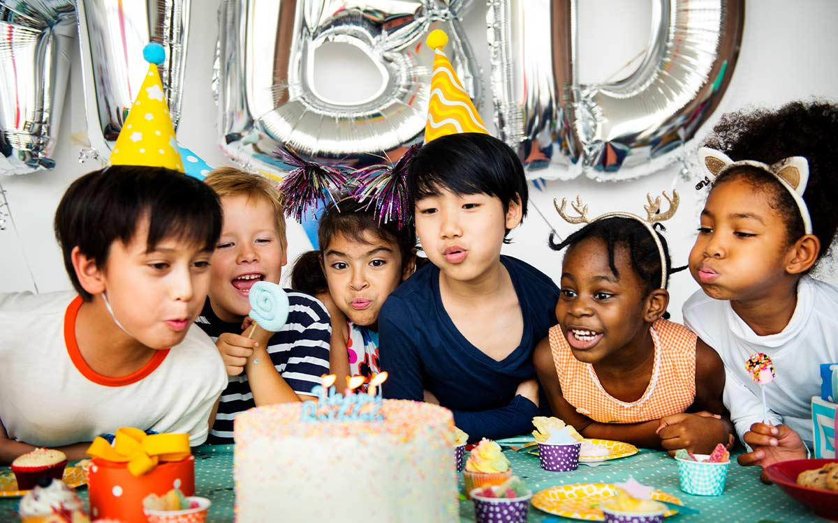 Kids blowing out the candles at a birthday party with friends at home.
