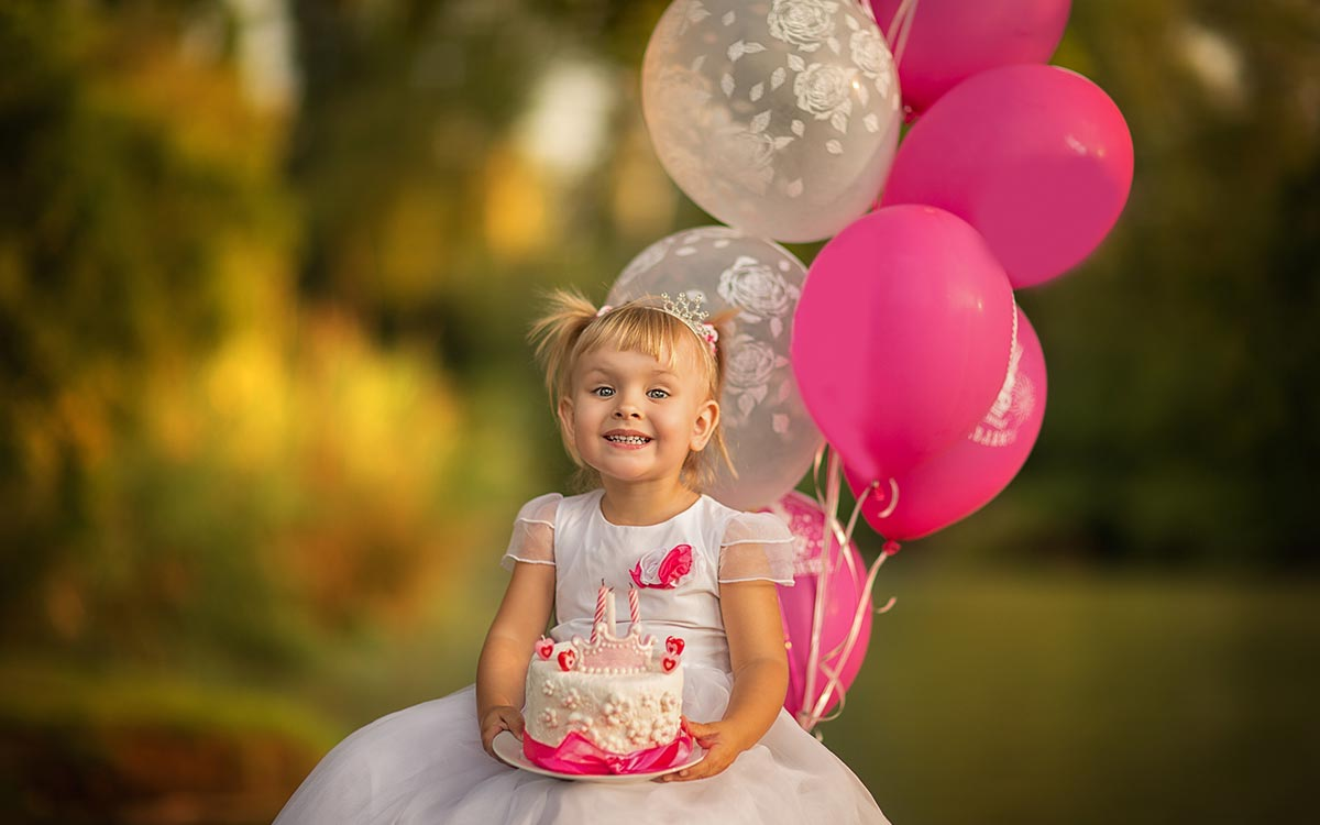 Little girl dressed in a pink princess outfit holding pink balloons in her garden at her party with family at home.