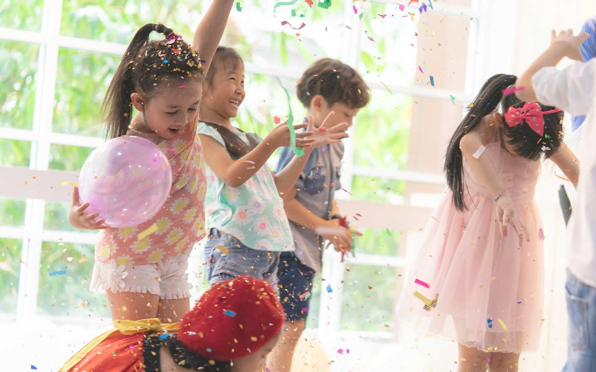 Happy kids jumping and dancing as they're showered with confetti at a birthday party.