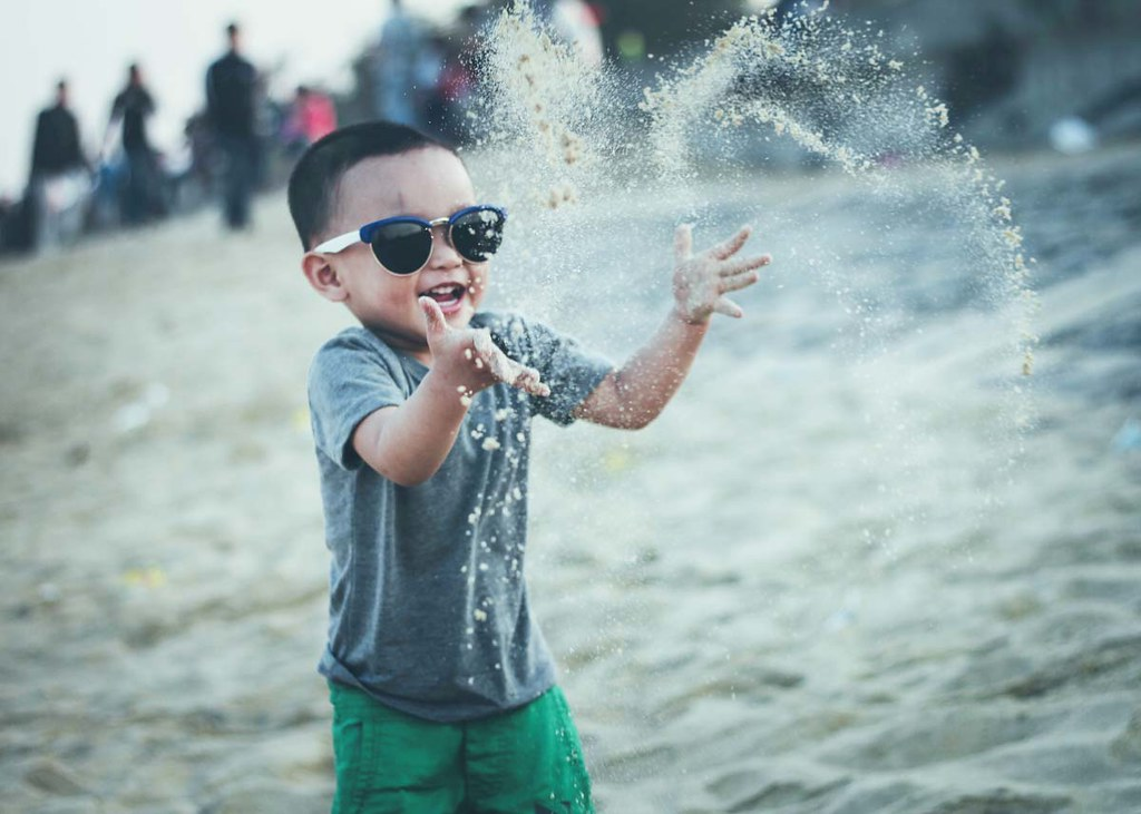 A little boy wearing sunglasses throws sand into the air at the beach.
