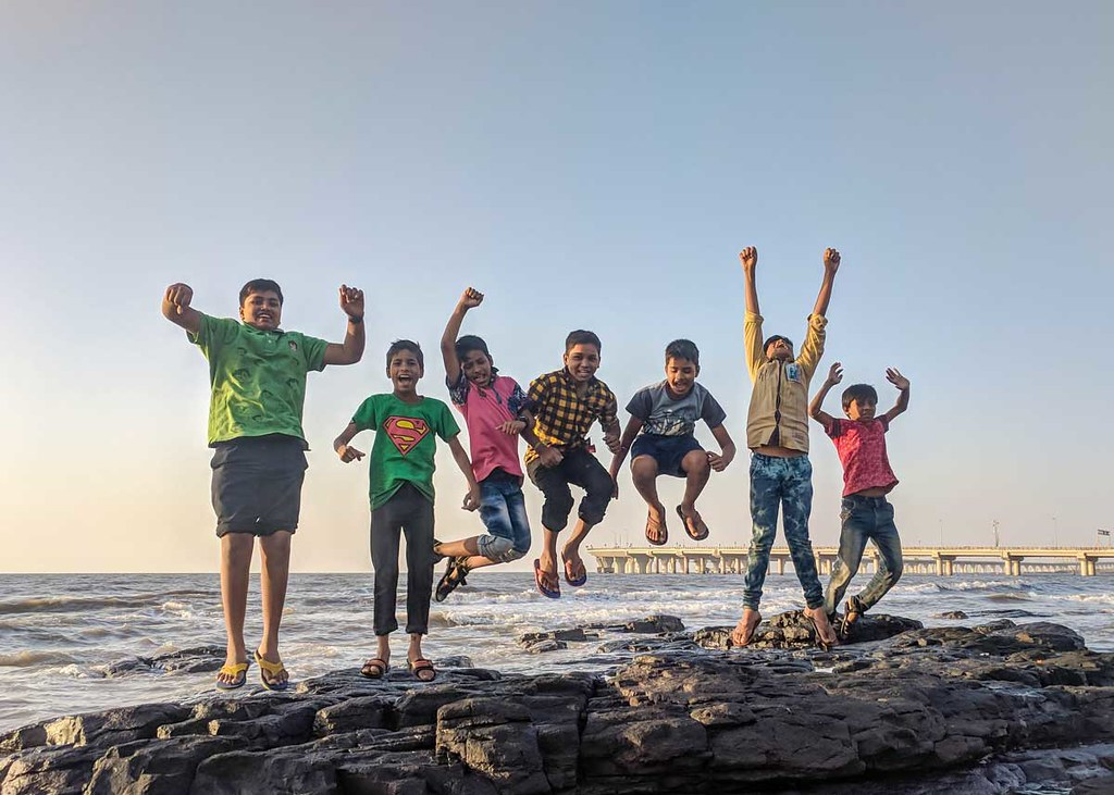 A group of young boys happily jump into the air at the beach.