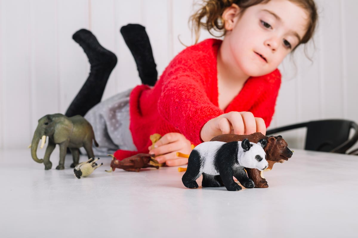 A young girl is lying on the floor playing with some animal toys.