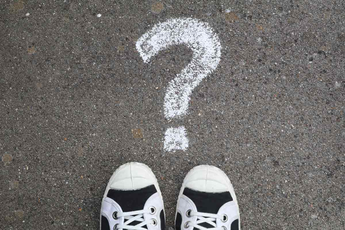 A mystery person's feet standing by a large question mark.