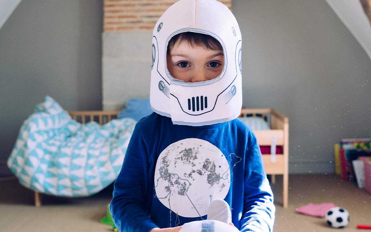 Boy wearing a homemade Stormtrooper helmet standing in his room waiting to hear Star Wars puns.