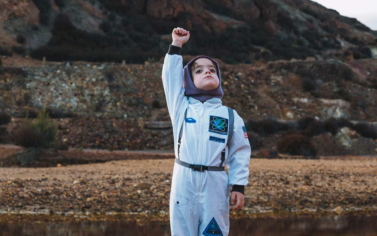 Child standing o rocky hills outside in an astronaut suit.
