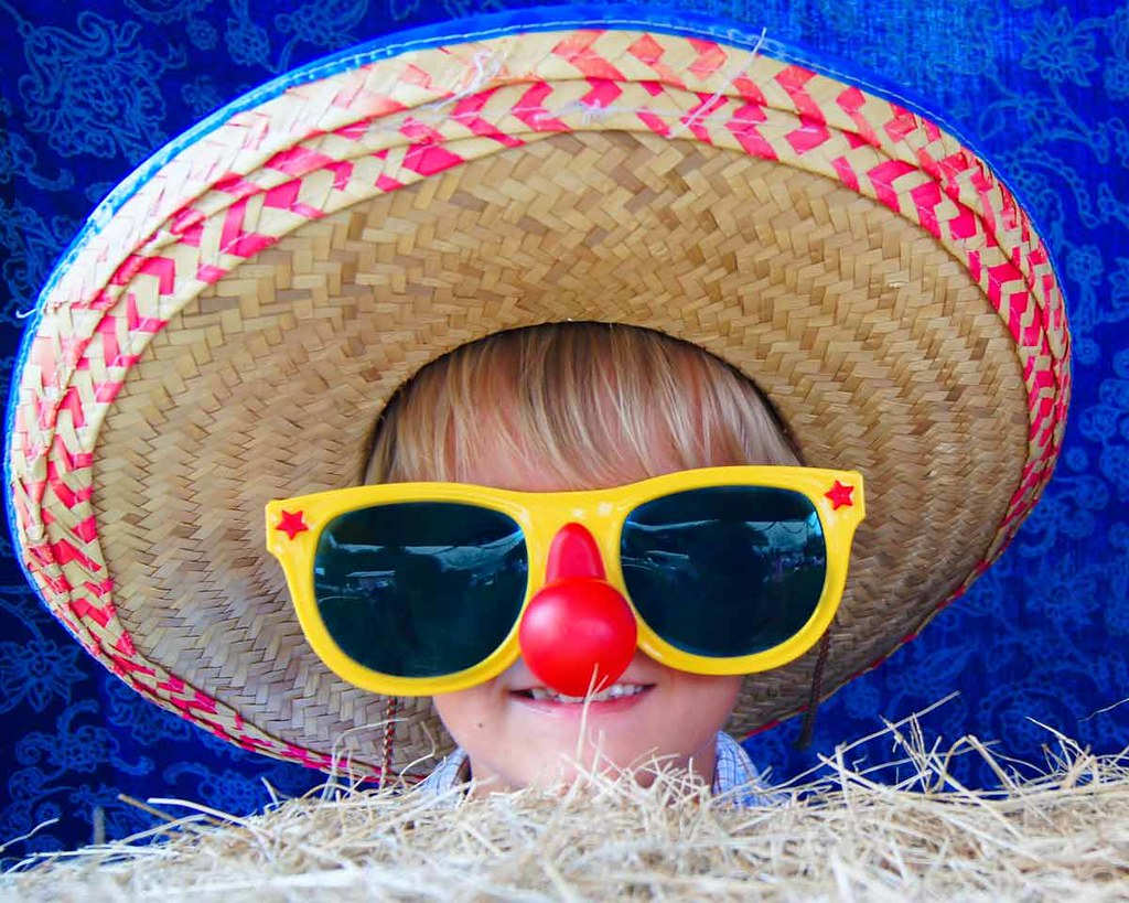 A young boy wearing a huge hat, big sunglasses and a red nose is smiling at the camera.