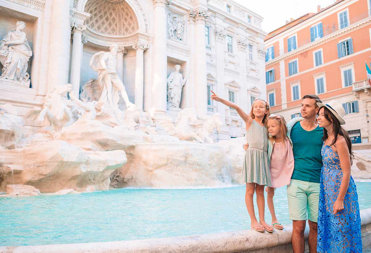 Happy family on holiday in Rome standing by the Trevi Fountain, little girl pointing to Roman architecture she learned about in school.