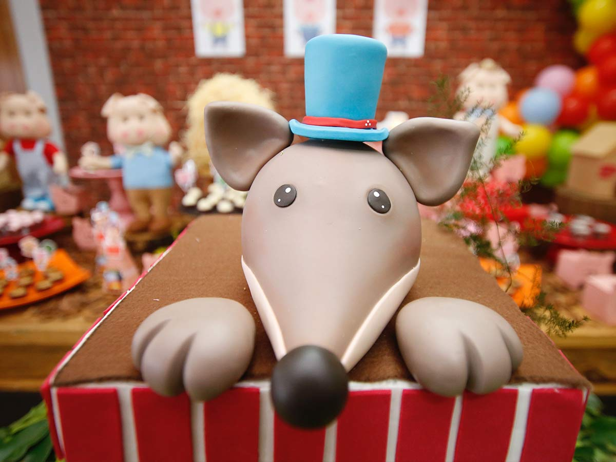 Birthday cake with a dog shaped icing on top wearing a top hat.