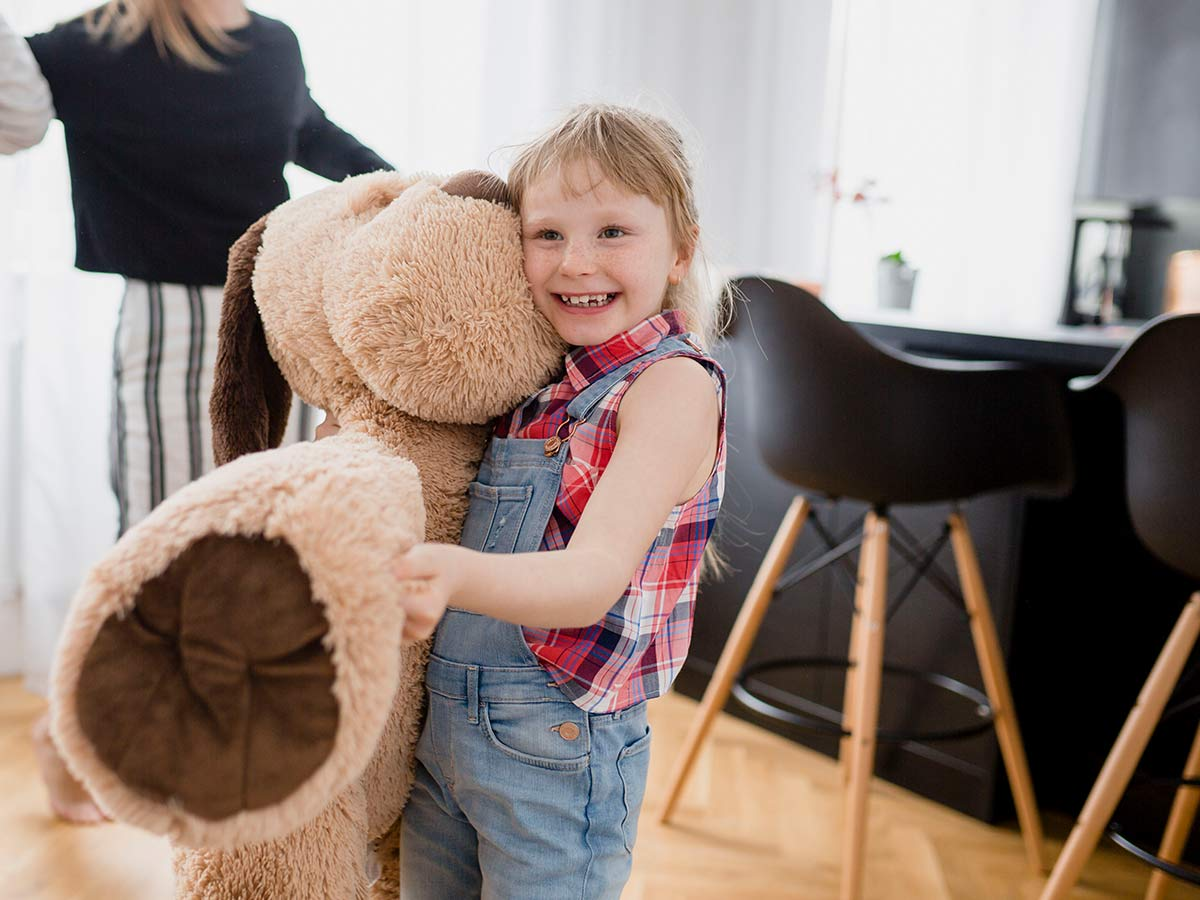 Little girl hugging a giant dog shaped soft toy.