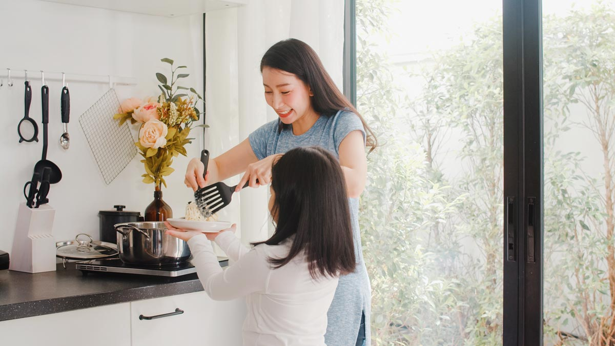 A mother and daughter are cooking rice together in the kitchen.