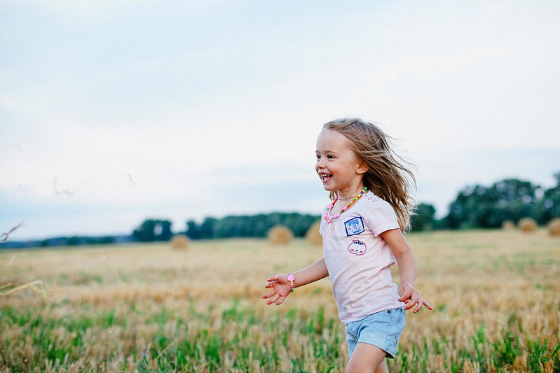 A little girl laughs as she runs through a field of crops.