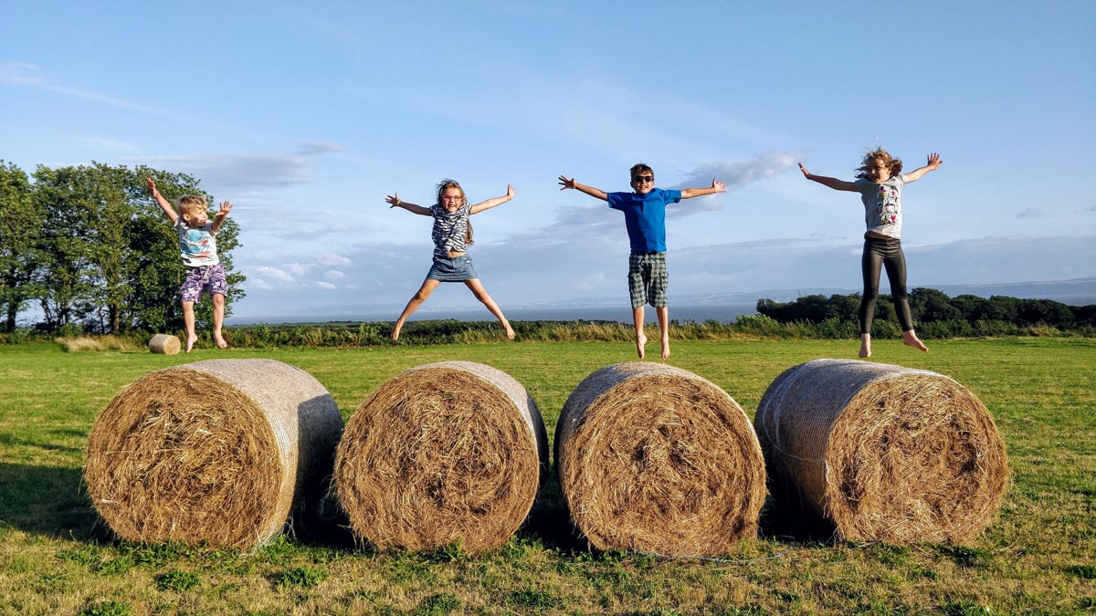 Four children jumping on hay bales at a farm.