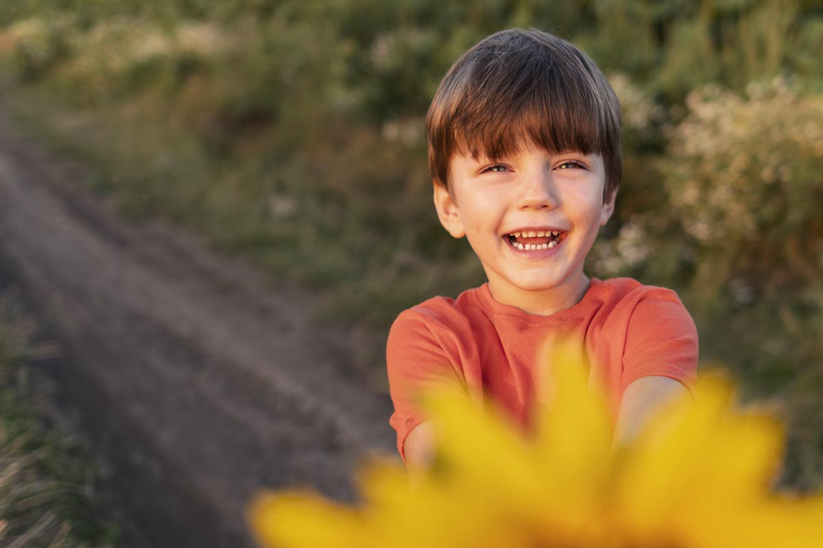 A young boy holding a flower laughs into the camera.