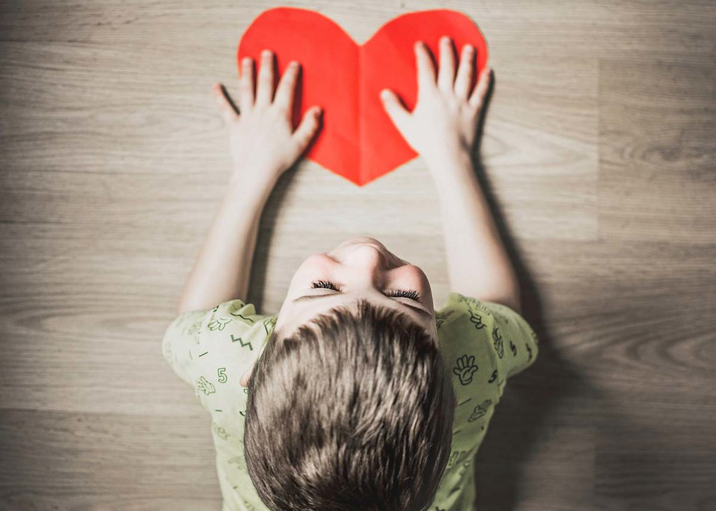 An image from above of a little boy holding a red heart cut out of cardboard.