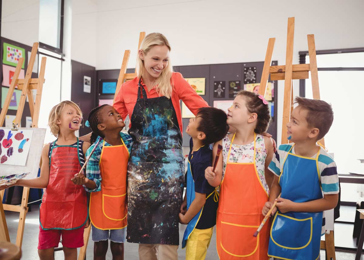 Art teacher standing next to a small class of students, smiling with her arms around them.