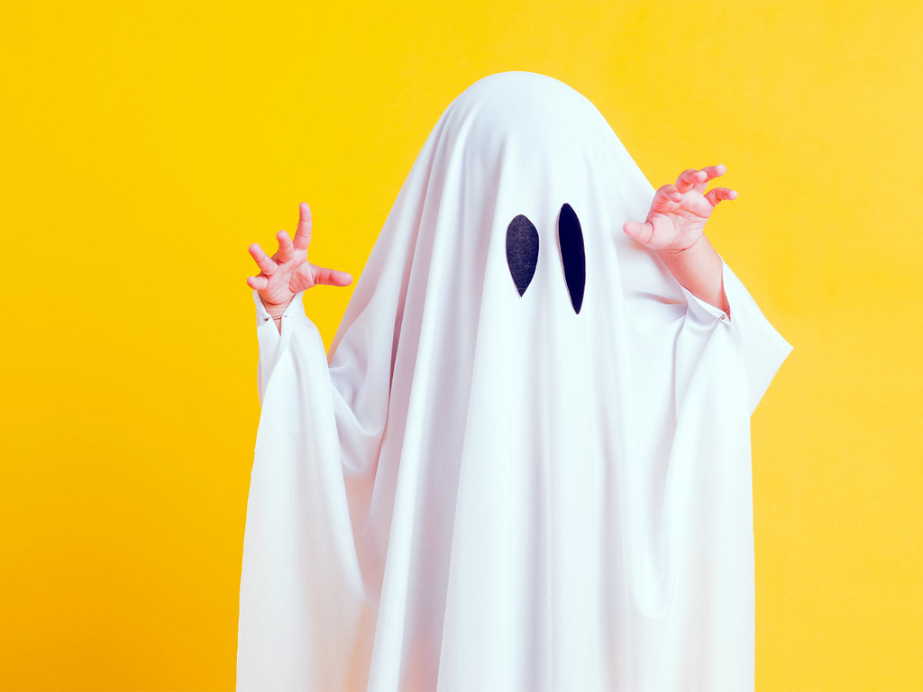 A child wearing a ghost costume poses in front of a yellow wall.