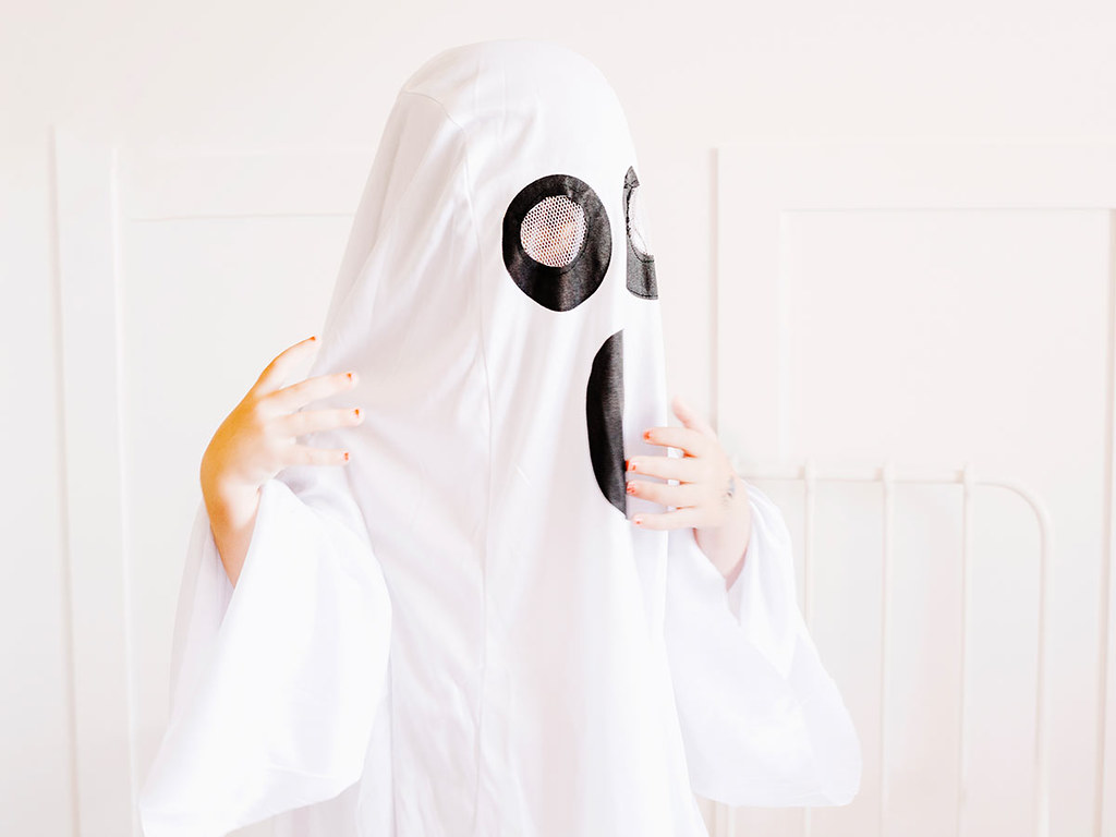 A child wearing a large white ghost costume.