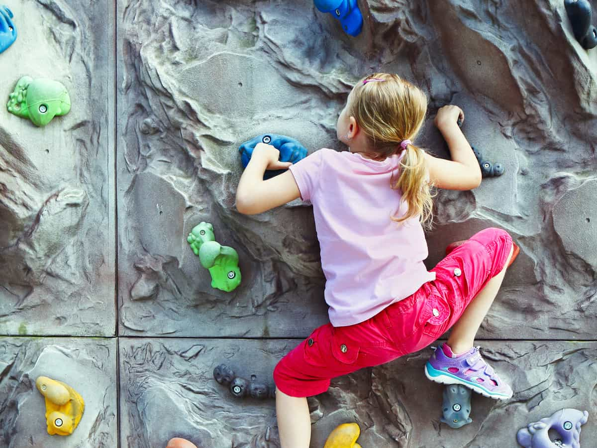Little girl wearing pink climbing up a rock wall.