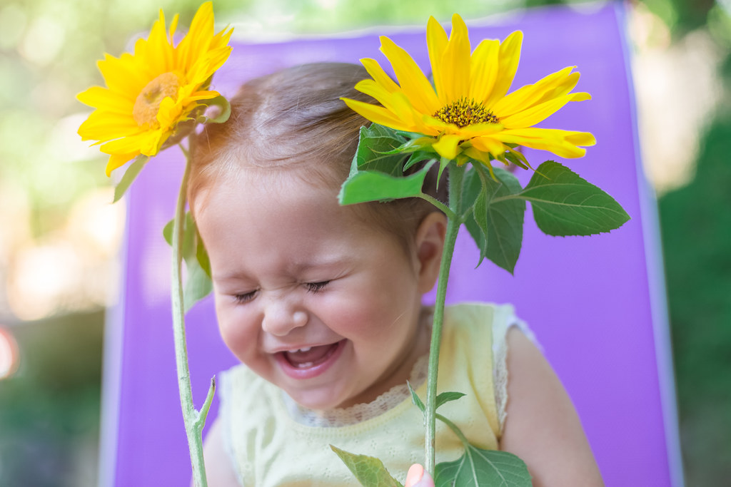 A young girl holding two sunflowers laughs at some spring jokes.