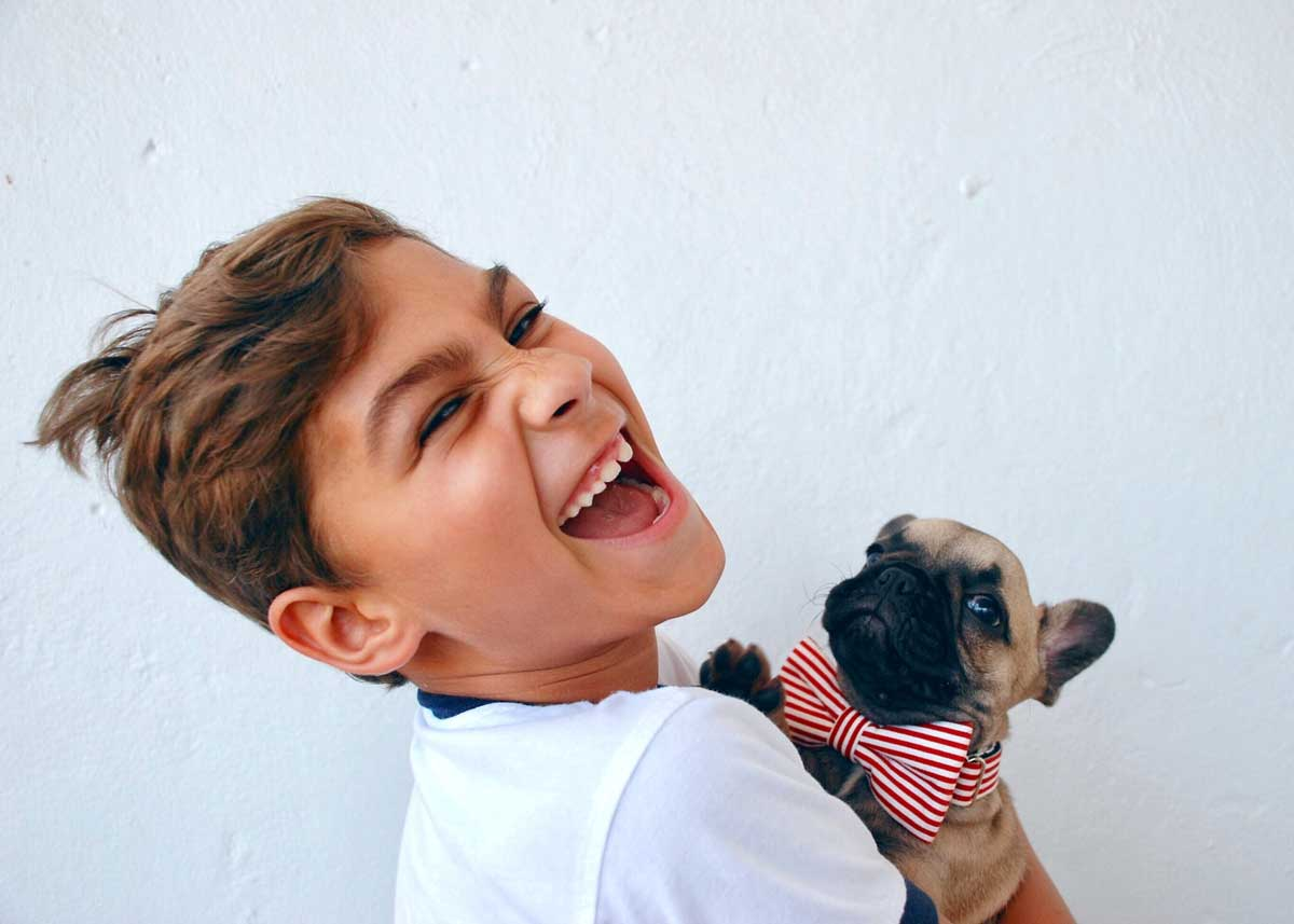 Young boy smiling while holding a pug wearing a bow.