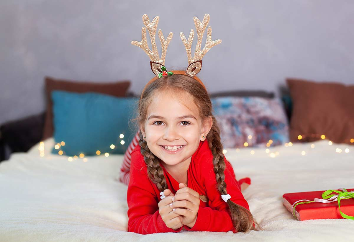 Little girl wearing gold deer antlers on her head, lying on the bed smiling.