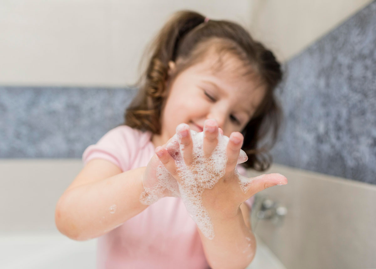 Little girl playing with soapy bubbles on her hand as she sits in the bath tub.