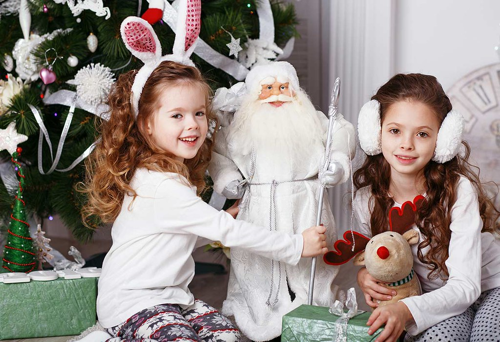 Two children are sitting surrounded by Christmas themed decorations and are smiling at the camera.