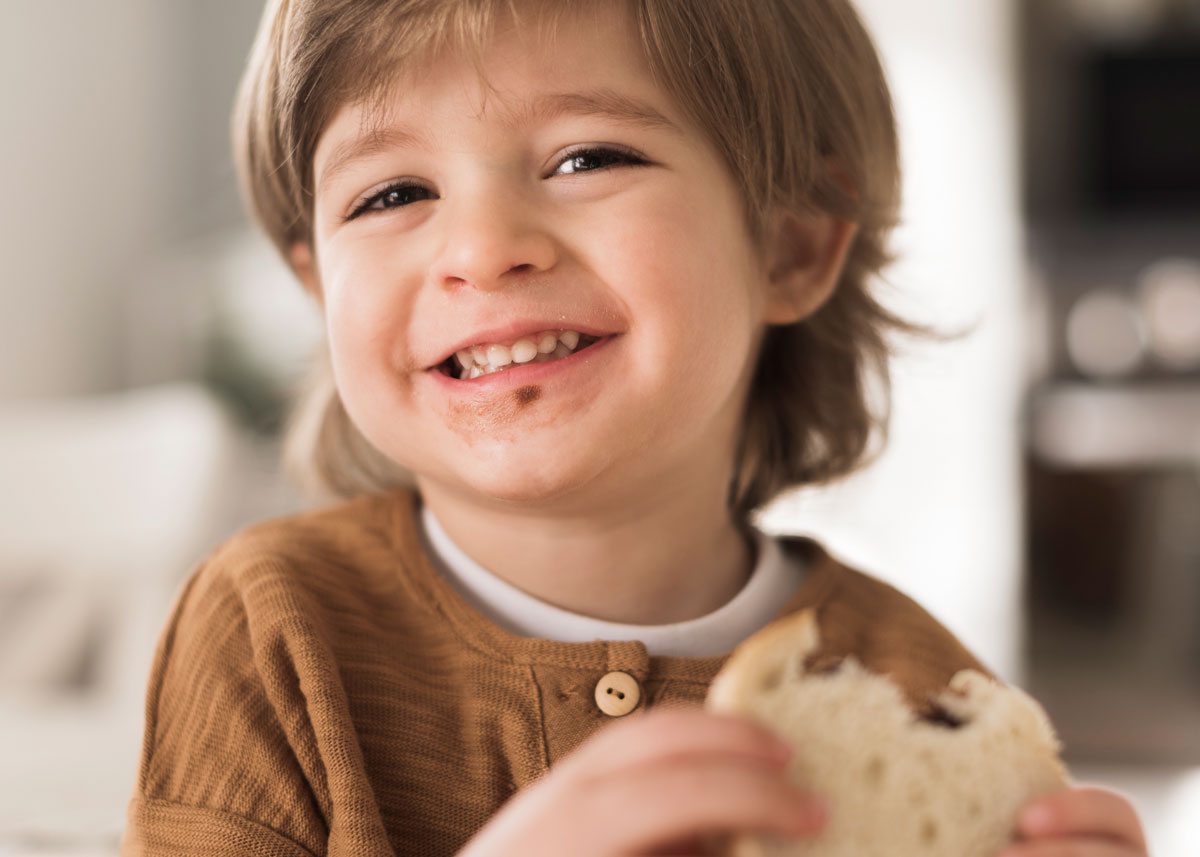 Little boy holding a sandwich in his hand as he eats it, smiling, with the brown filling on his face.