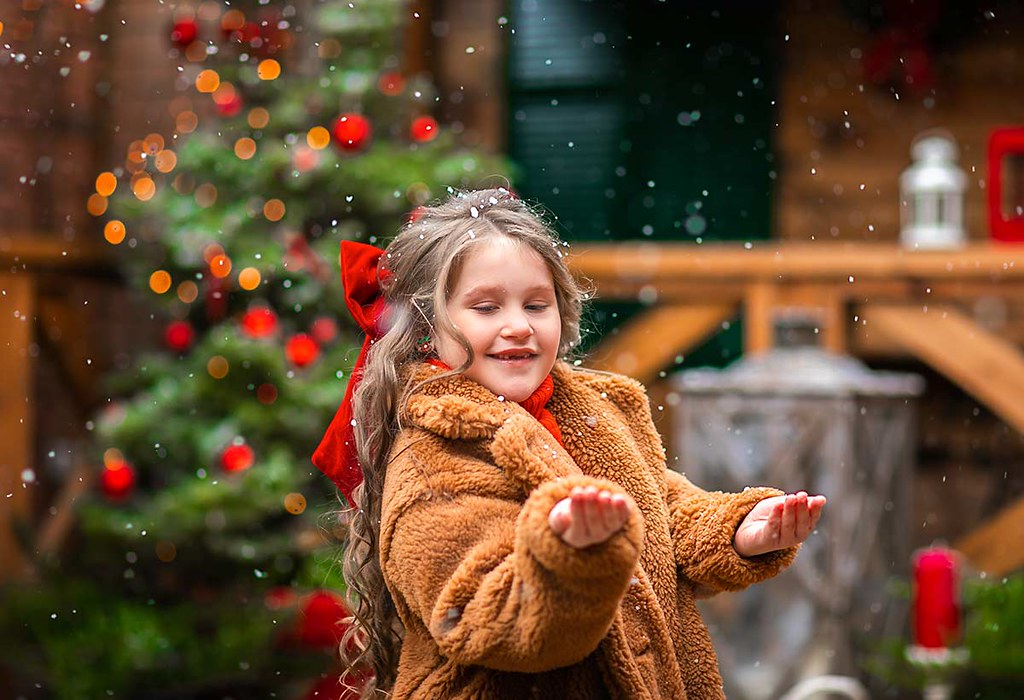 A little girl puts her hands out to catch falling snow at Christmas time.