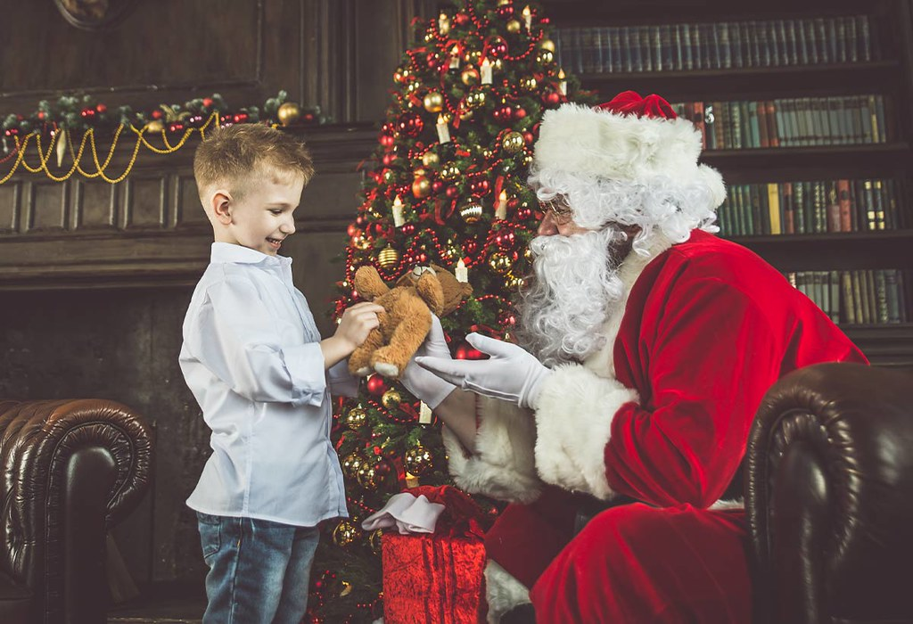 A little boy meeting Father Christmas in a Christmas grotto.