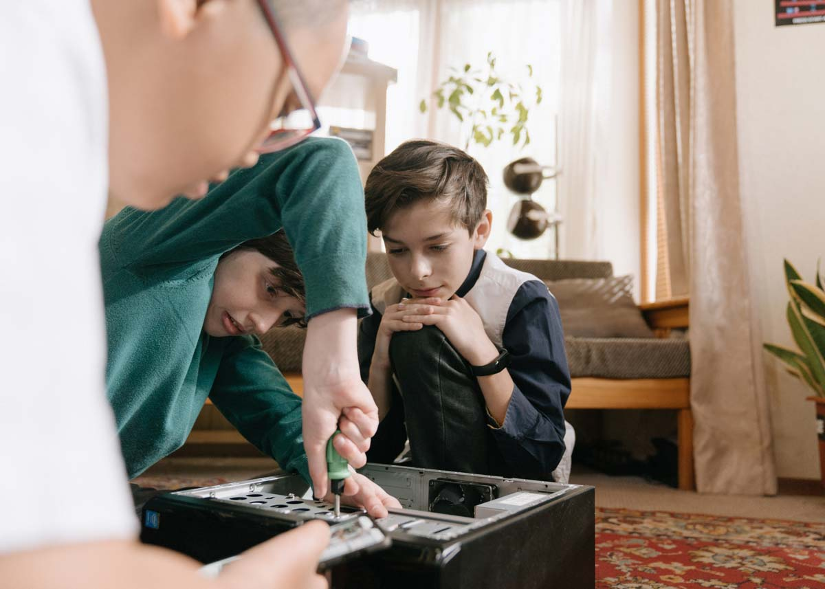Young boys fixing the electronics with a screwdriver, like electrical engineers.
