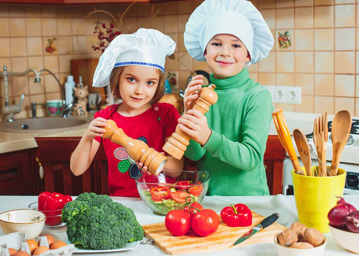 Two kids standing in the kitchen wearing chef's hats as they season a salad in the bowl.