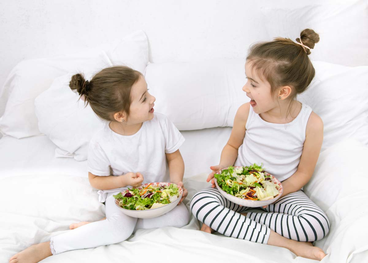 Two sisters sit on the bed smiling at each other whilst holding a bowl of salad in their hands.