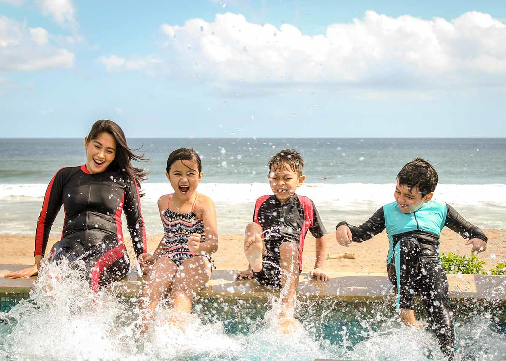 A family wearing wetsuits smile as they splash sea water with their feet at the beach.