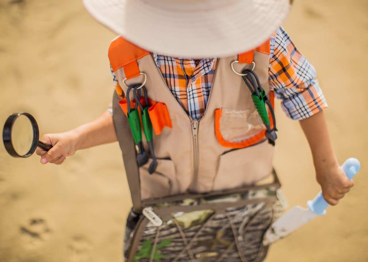 Little boy dressed as a geologist, wearing a hat and a vest with tools in it, holding a magnifying glass in his hand.