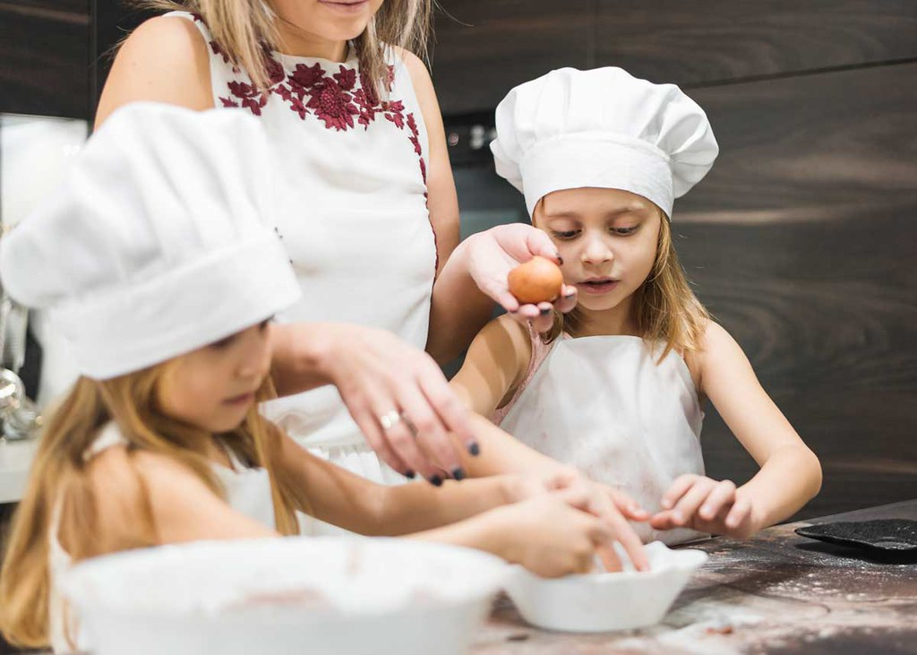 Two girls wearing chef hats are baking some food together with their mum.
