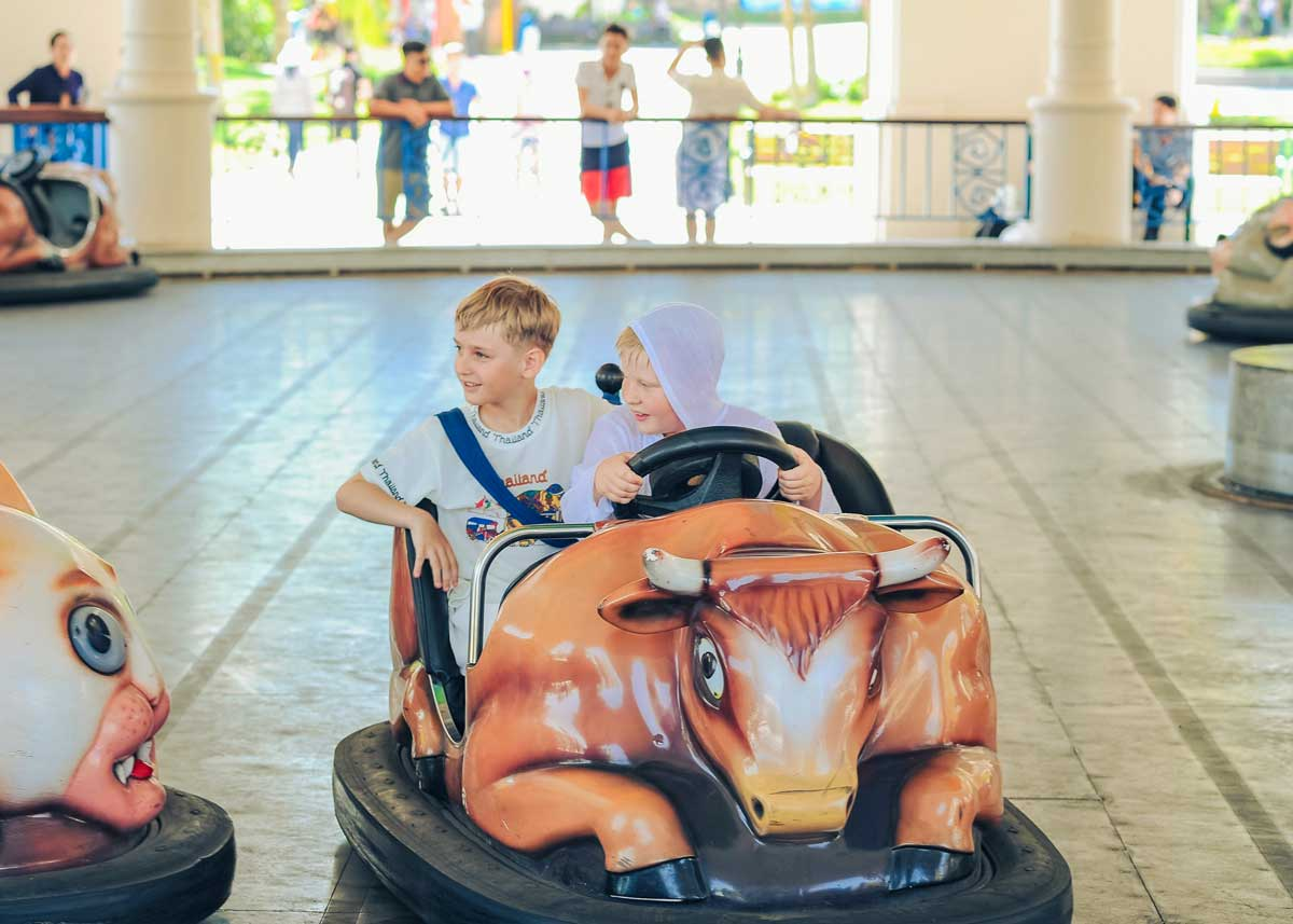 Two boys sat driving in a bumper car smiling and having fun.