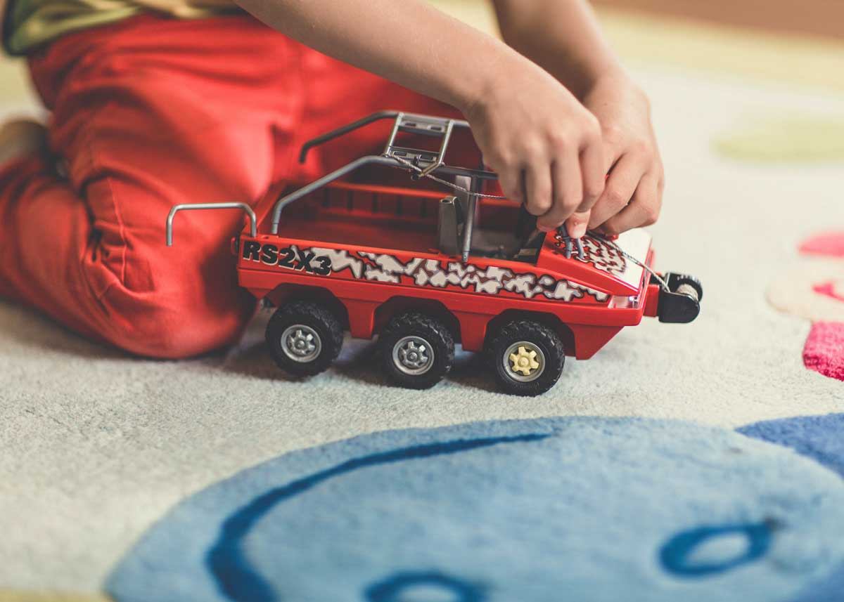 Close up of a child kneeling on the floor playing with their red toy truck.