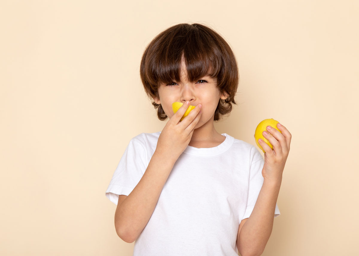 Boy standing in front of a yellow background pulling a face as he eats a sour lemon.