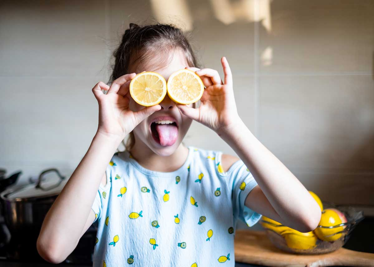 Girl wearing a top with lemon print on it, holding up two halves of a lemon as bug eyes and sticking her tongue out.
