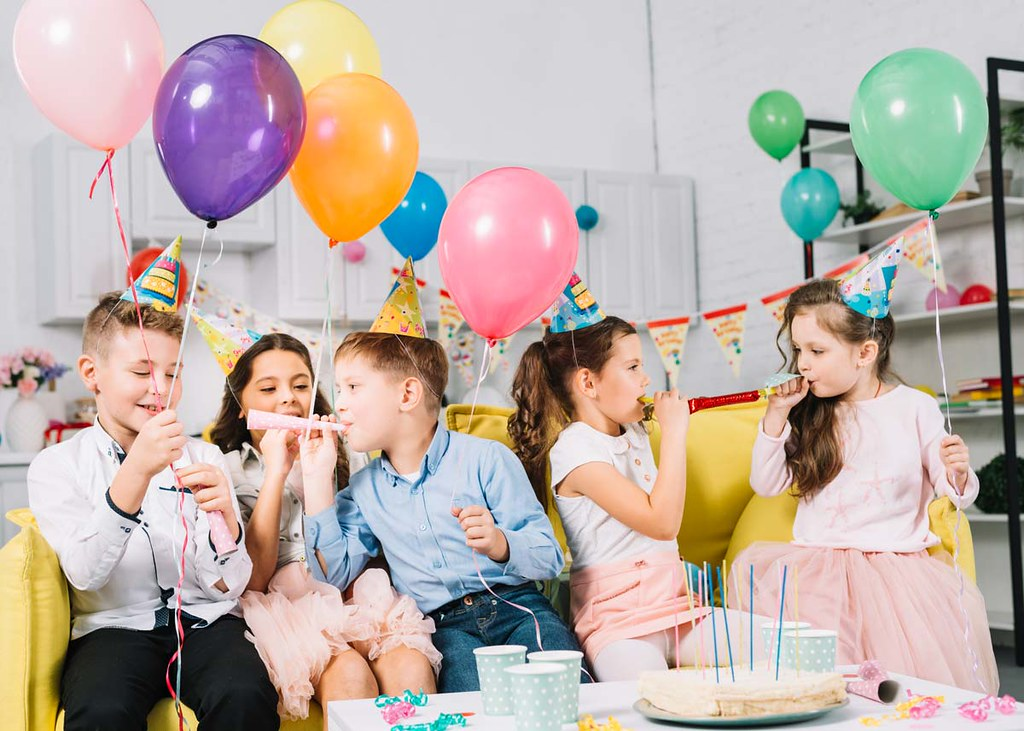 A group of children are sat amongst lots of balloons and other birthday party decorations.
