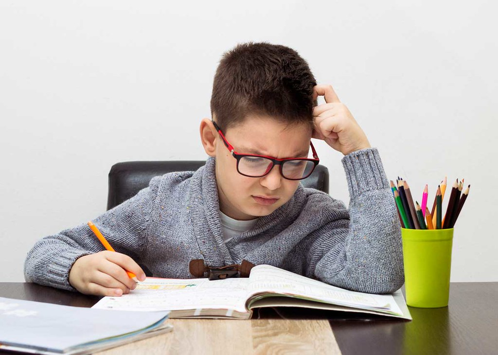 A boy is sat at his desk looking puzzled as he tried to work out some science riddles.