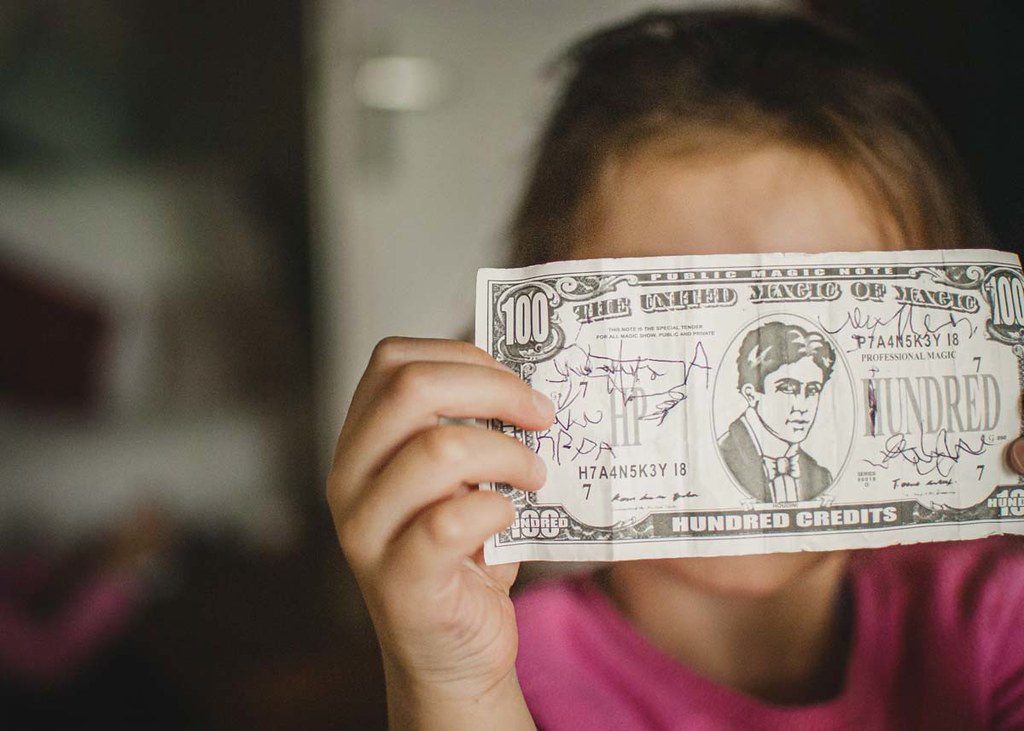 A close up image of a little girl holding some money up to the camera.