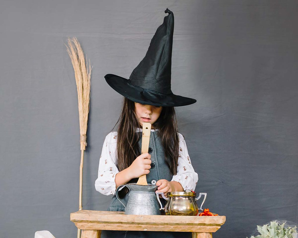 A little girl dressed as a magical witch is casting spells.